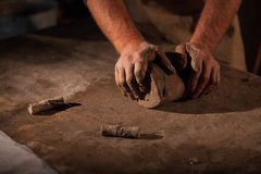 Hands of the potter knead clay. Kneads crude clay on a table Royalty Free Stock Images