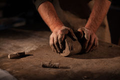 Hands of the potter knead clay. Kneads crude clay on a table Royalty Free Stock Photos