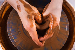 Hands of potter on  pottery wheel Stock Photos