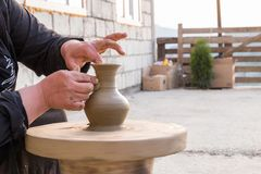 Hands of a potter woman make a pitcher of clay in the courtyard of the house stock photography
