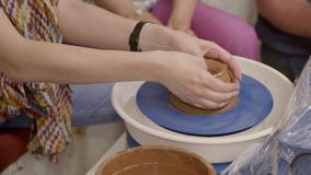 Hands of a Potter. Hands of a woman potter makes on the pottery wheel clay pot.Creating an earthen jar on the circle at master class in slow motion. Hobby stock footage
