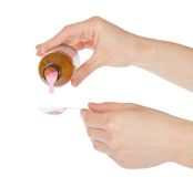 Hands pour pink medicine in a spoon Stock Photo