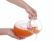 Hands poured from a carafe of  juice. Hands of the girls poured from a carafe of fresh juice Royalty Free Stock Photos