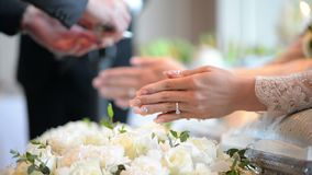Hands pouring blessing water into groom and bride bands, Thai wedding stock video footage