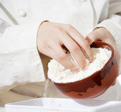 Hands pouring flour on scales Royalty Free Stock Image