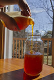 Hands Pouring Honey From a Jug Into a Jar Stock Photography