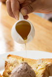 Hands are pouring honey on toast Royalty Free Stock Photos