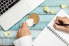 Hands pouring milk in coffe cup and writing in notebook on workp Royalty Free Stock Images