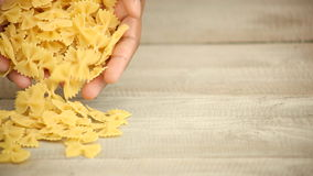 Hands pouring pasta onto wood. Male hands pouring Mezze Maniche pasta onto wood stock footage