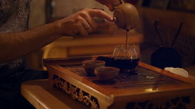 Hands Pouring The Tea From the Glass Kettle Into Two Cups. stock video footage