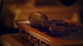 Hands Pouring The Tea From the Glass Kettle Into Two Cups. Chinese Traditional Tea Ceremony Element Indoor Footage stock video