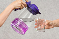 Hands pouring water from a jug into a glass. Of another person Royalty Free Stock Photo