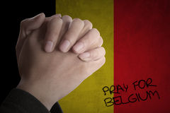 Hands pray for Belgium with Belgian flag. Picture of hands posing pray for Belgium in front of Belgian flag background royalty free stock images