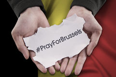 Hands pray for Brussels with a paper piece Stock Photo
