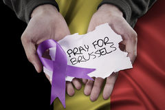 Hands pray for Brussels with ribbon. Image of hands holding a ribbon shaped a sorrow sign with text to pray for Brussels Stock Images