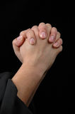 Hands in prayer. On dark background Royalty Free Stock Images