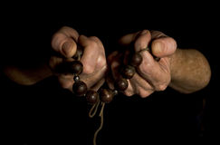 Hands with Prayer Beads. Elderly hands holding prayer beads in reduced lighting Stock Photos