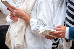 Hands and prayer book close-up. Orthodox hassidic Jews pray in a holiday robe and tallith.  stock photos