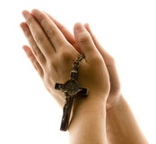 Hands in Prayer with Crucifix. Religious and Spirituality presentation depicted through a female hand in prayer on white with a crucifix clutched in between Royalty Free Stock Photos