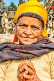 Hands in prayer in Nepal. Pathivara Devi, Nepal - circa May 2012: Old woman with yellow headcloth and piercing in her nose with her hands in prayer in Pathivara Royalty Free Stock Image