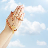 Hands  in prayer with a rosary. Hand with a rosary against blue sky Royalty Free Stock Images
