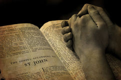 Hands Praying on Bible. Hands of a person raised together in prayer with bible royalty free stock images