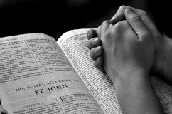 Hands Praying on Bible Black and White. Hands of a person raised together in prayer with bible stock photography
