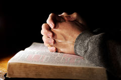 Hands Praying Bible Man. A man's hands in a serene setting as he prays over his Holy Bible (Christian Image, shallow focus royalty free stock photography