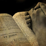 Hands Praying on Bible. Hands of a person raised together in prayer with bible stock photography
