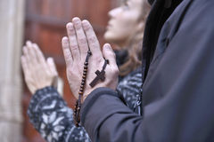Hands of a praying couple holding prayer beads. In church royalty free stock photography