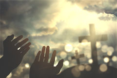 Hands praying with cross on sky. Picture of hands praying to the GOD with three crosses symbol and bright sunbeam on the sky Royalty Free Stock Photos