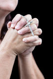 Hands praying and holding a small crucifix Stock Photo