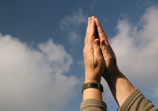 Hands praying to heaven. Sky background. Clasped hands together praying. A blue sky and white cloud background stock photography