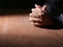 Hands Of Praying. Praying hands of young man on a wooden desk background stock photo