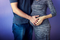 Hands on pregnant abdomen. Mans and womans hands lying on pregnant abdomen Stock Photos