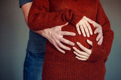 Hands on pregnant abdomen. Mans and womans hands lying on pregnant abdomen Stock Images