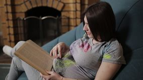 Pregnant woman reading a book. Hands of pregnant woman caressing belly while reading book stock video footage