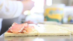 Hands prepare a sandwich with cheese and ham stock footage