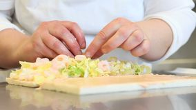 Hands prepare a sandwich with shrimp and lettuce stock video