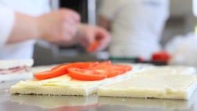 Hands prepare sandwich with tomato mozzarella stock video