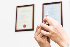 Hands preparing injection syringe against backdrop of medical certificates.  royalty free stock images