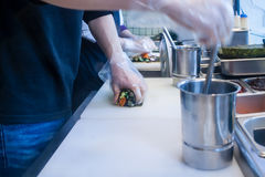 Hands preparing korean rice rolls Stock Photos