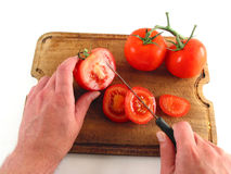 Hands preparing tomatoes. Hands slicing juicy tomatoe on wooden plate Royalty Free Stock Image