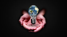 Hands presenting light bulb with earth stock footage