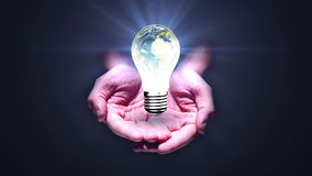 Hands presenting light bulb with earth stock video