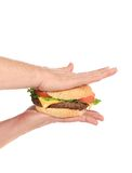 Hands press juicy hamburger. Royalty Free Stock Photos