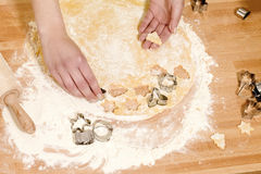 Hands pressing christmas molds in dough Royalty Free Stock Photography