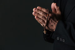 Hands of priest holding rosary and praying Royalty Free Stock Photo