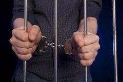 Hands of the prisoner on a steel lattice Stock Image