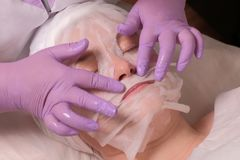 The hands of a professional cosmetologist in lilac gloves impose a nourishing mask on the patient. Cosmetic mask on a woman`s fac. The hands of a professional royalty free stock photos